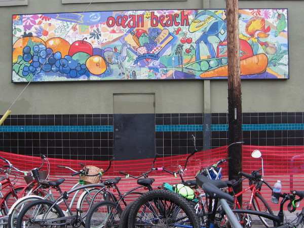 Another street mural on a wall above a station where people could park their bikes.