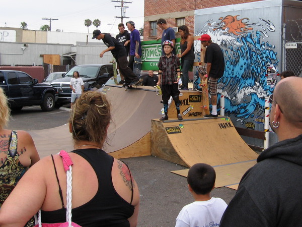 Lots of skilled skateboarders were taking turns on this small half-pipe.