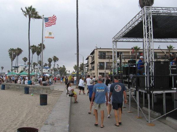 People walk behind the Main Stage along the beach, toward the Ocean Beach lifeguard station. An overcast day with a few sprinkles, but it didn't matter!