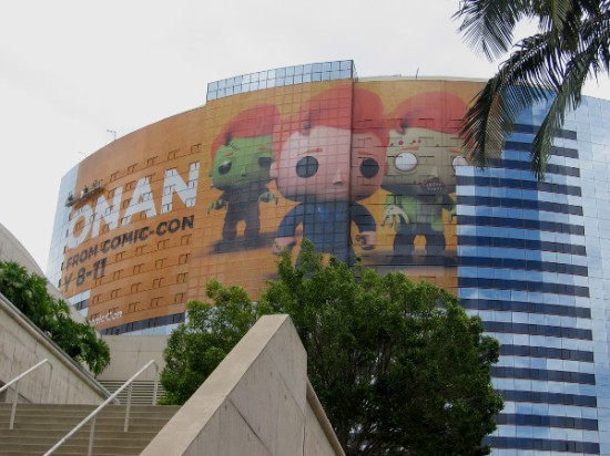 A gigantic orange Conan O'Brien building wrap is being applied to the side of the Marriott Hotel facing the San Diego Convention Center.