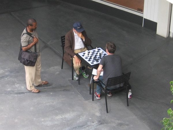 Horton Plaza visitor watches two people playing chess on an ordinary-size chessboard.