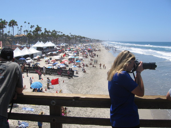 Camera aims toward surfing action from the Oceanside Pier during 2015 Supergirl Pro World Surf League (WSL) competition.