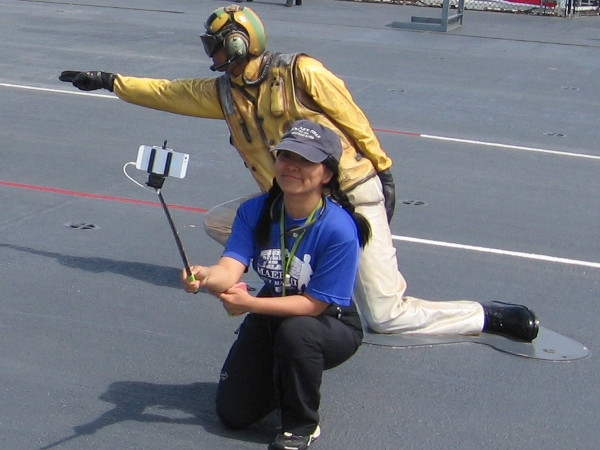 USS Midway visitor takes photograph with selfie stick next to aircraft launching Shooter mannequin.