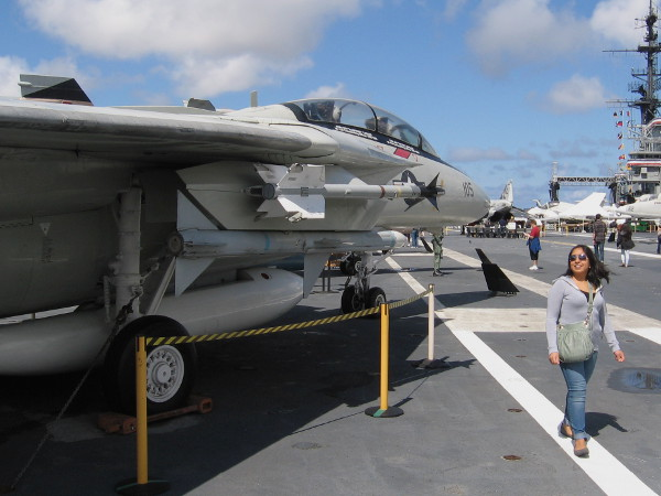 Lady walks past F-14 Tomcat fighter jet on USS Midway aircraft carrier's flight deck.