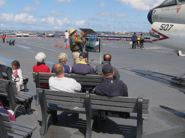 People sit on benches listening to a docent talk about launching airplanes from Midway's two steam-powered catapults.