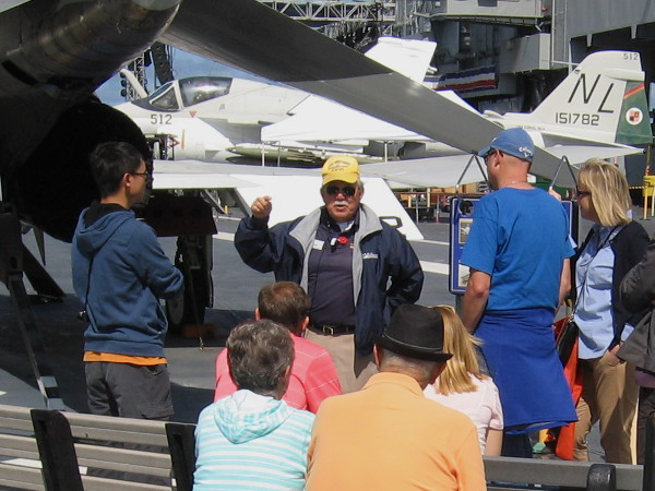 Docent veteran talks about how aircraft landed on the flight deck using tailhooks and arresting cables.