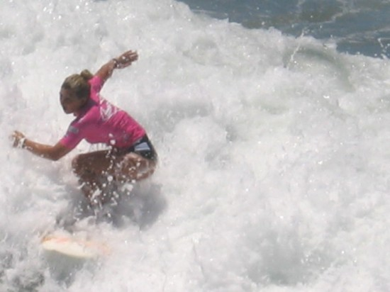 Professional World Surf League (WSF) Supergirl Pro Women's Qualifying Series surfer rides the foam in Oceanside, California.