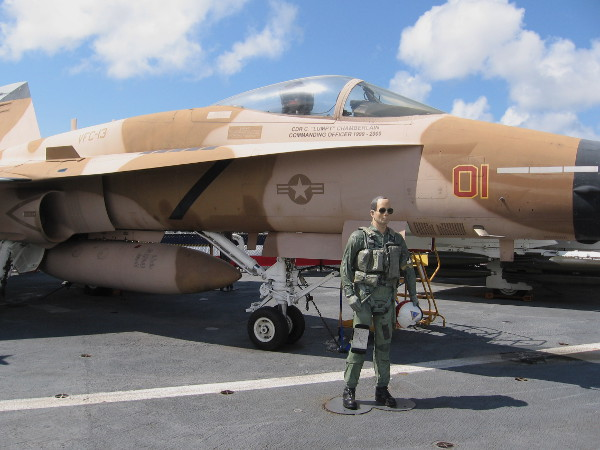 Navy pilot mannequin in flight suit stands near FA-18 Hornet, painted as a TOPGUN enemy aircraft.