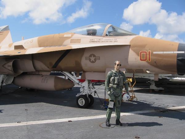 Navy pilot mannequin in flight suit stands near FA-18 Hornet, painted as a TOPGUN enemy aircraft.