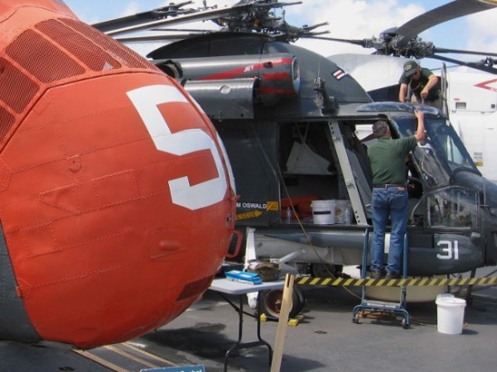 Volunteers work to restore SH-2 Seasprite, beyond orange nose of H-34 Seabat.