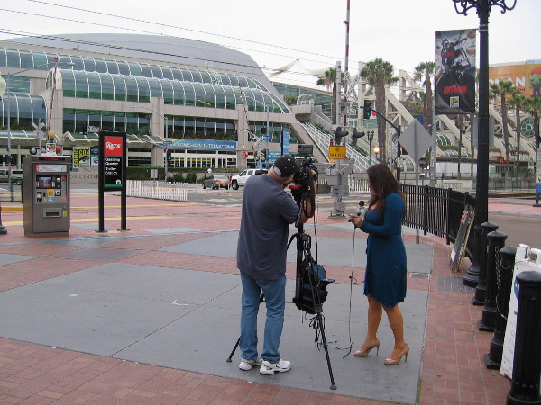 A local television news reporter stands near entrance to the Gaslamp, previewing 2015 Comic-Con on camera.