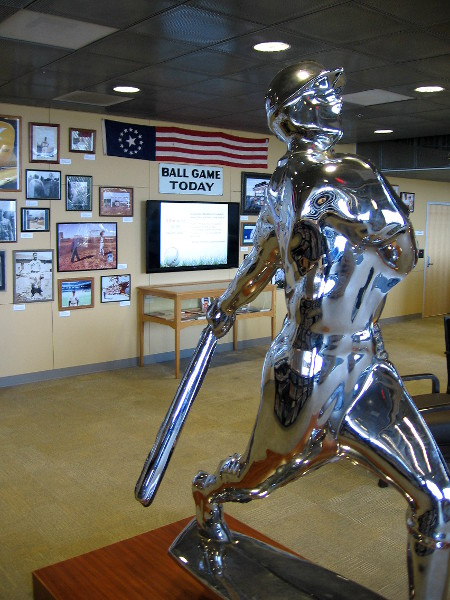Bronze and chrome Yoram Wolberger statue of a baseball player swinging a bat.