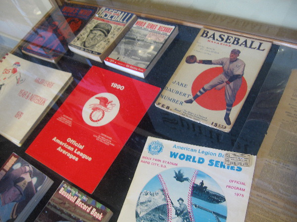 Photo of one display case, which contains a copy of Baseball Magazine, plus various programs and record books.