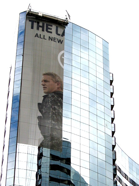 A suspended platform is used to adhere panels of a The Last Ship building wrap to windows of the shining Marriott Marquis.