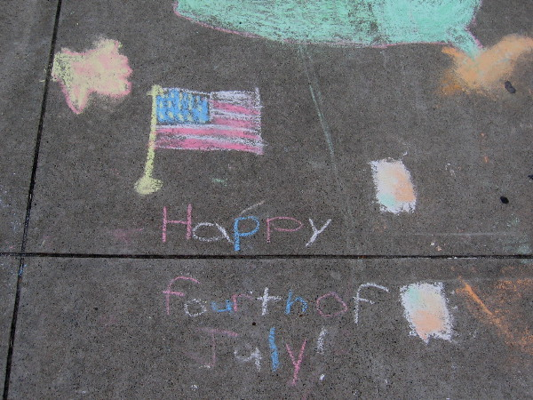 Someone wrote on the sidewalk with chalk: Happy Fourth of July!