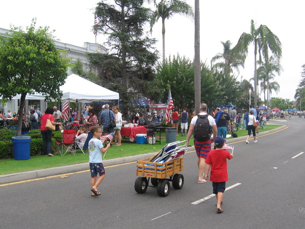Kids with flags follow a big wagon full of lawn chairs, as the parade is almost ready to start.