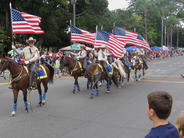 The Escondido Mounted Posse carry flags.