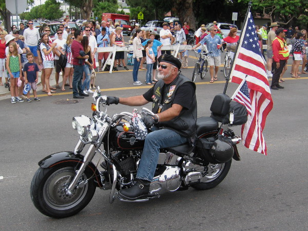 An American military veteran rides his motorcycle down Orange Avenue.