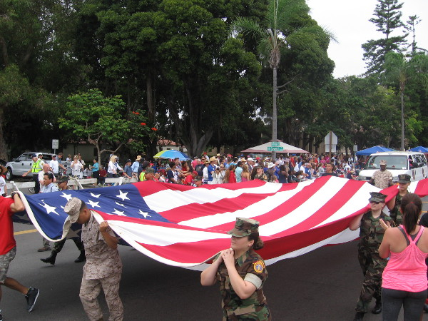 San Diego heroes carry a large American flag.