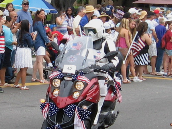A biker scout trooper clears a path for the San Diego Star Wars Society with a flag-festooned, red, white and blue patriotic motorcycle!