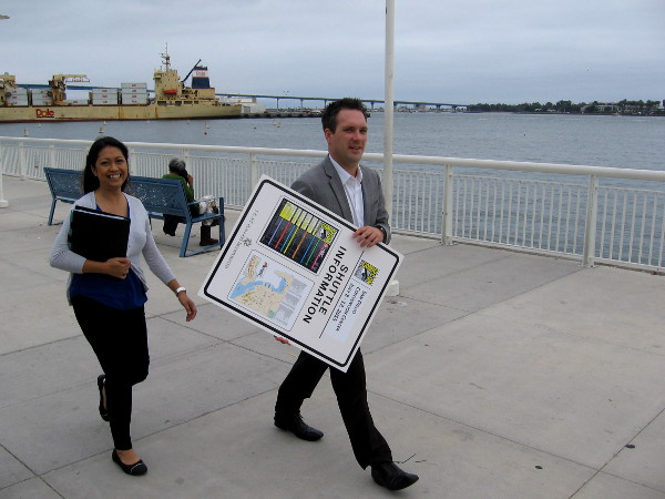 These smiling folks were heading along the bay walkway with a sign containing Comic-Con shuttle information.