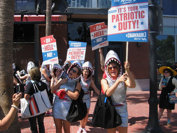 Ladies in Sharknado 3 shark heads hold signs indicating It's Your Patriotic Duty to Embrace the 'Nado!