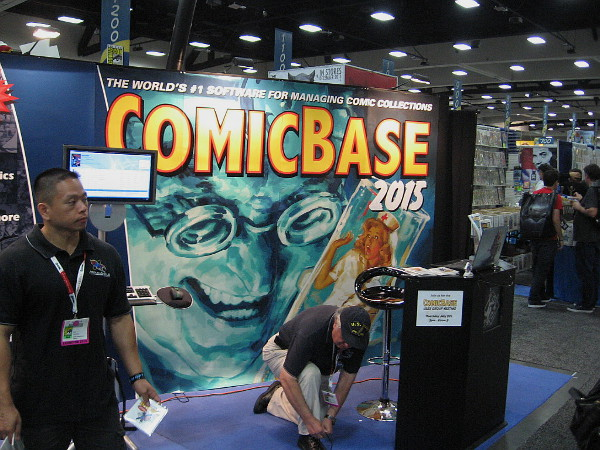 Sinister face on large ComicBase software graphic seems to be looking down at an exhibitor as he ties his shoelace!