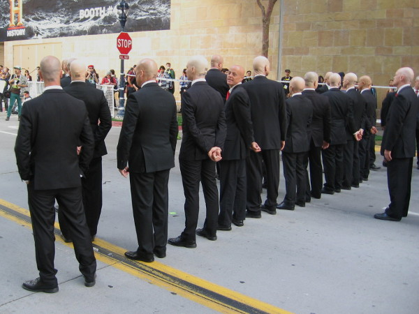 These suited bald guys with barcode tattoos on their necks are lined up to promote Hitman, Agent 47.