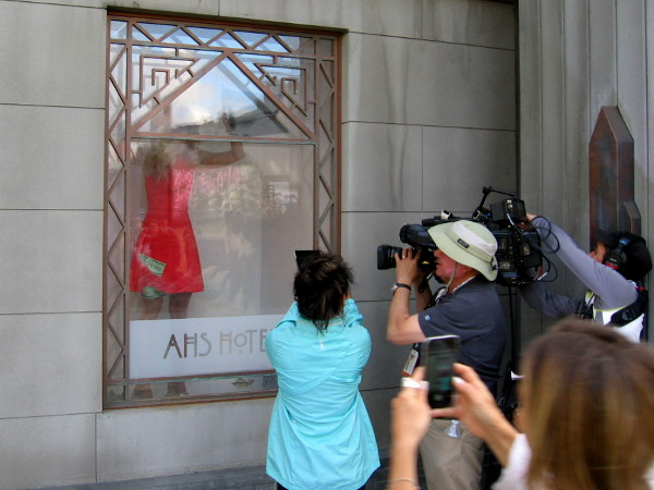 Model grabs at swirling dollar bills in window of American Horror Story Hotel while being filmed.