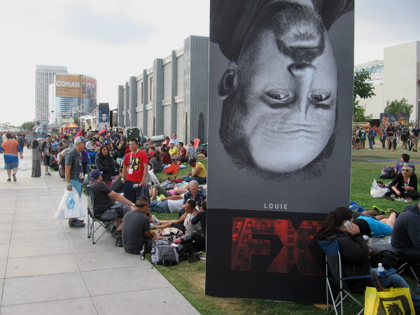 Upside down Louie seems to wait in line for Hall H with thousands of Comic-Con fans. They'll be sleeping outside all night on the grass or concrete. That's dedication!
