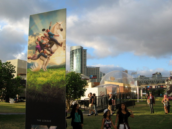 Folks riding a unicorn prepare to launch above the Omni Hotel into the cloudy blue sky, over a gigantic bubble resting on the grass!
