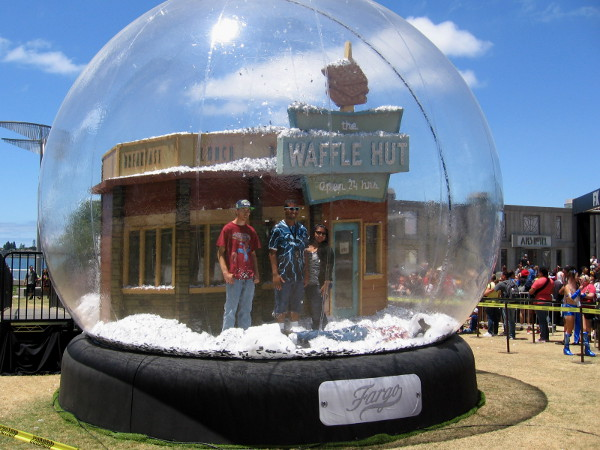 Fargo fans stand in a glitter-filled huge snow globe for a photograph!