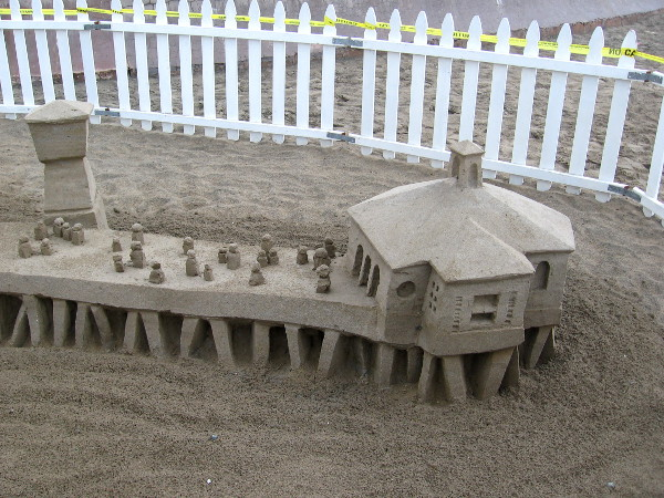 A second photo of Kirk Rademaker's sculpture. Tiny sand people stand out on a sand IB pier over the sandy Pacific Ocean!