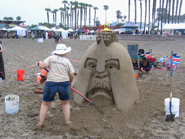 Sandstorm Fabrication team seems to be creating a large Viking head sand sculpture.