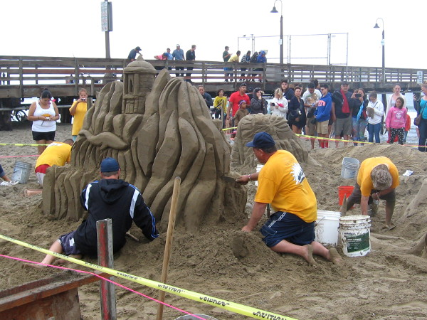 The I.B. Posse team is crafting a complex, exotic scene of Myths and Legends out of sand near the Imperial Beach pier.