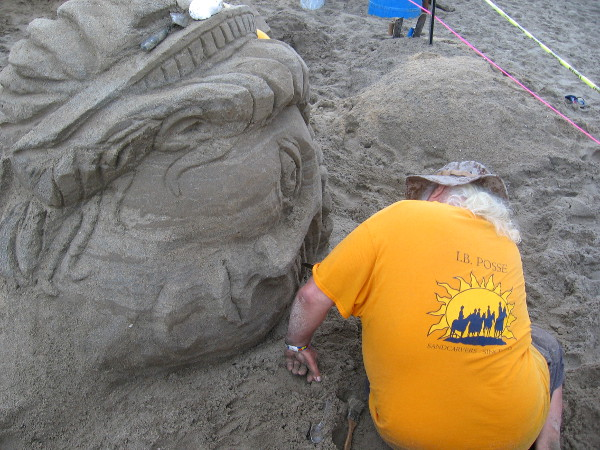 Sand sculptor is closely watched by the unblinking eyes of an inanimate subject.