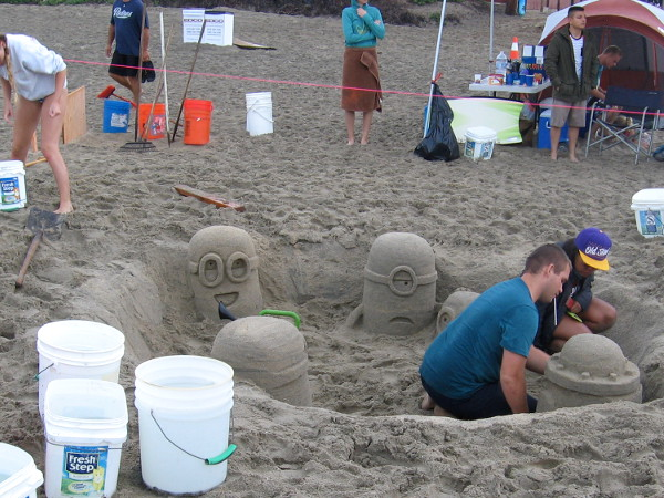 Five silly Minions seem to be having a party in a sand pit.