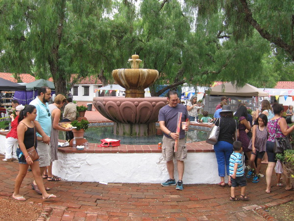 Folks hang out around the central fountain, eating yummy food and taking in sights, smells and sounds during a lively San Diego tradition.