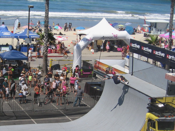 People watch an athlete defy gravity on the halfpipe at 2015 Supergirl Pro!