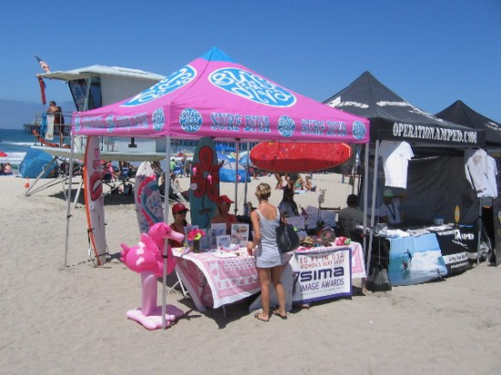 The Surf Diva has a big pink canopy on the sand!