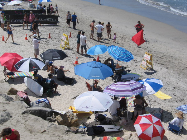 Folks in the shade of beach umbrellas look toward the surf, where dueling Supergirls are performing astonishing feats during 25 minute heats.