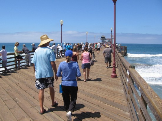 Walking farther out on Oceanside Pier to get closer to the powerful Pacific Ocean breakers.