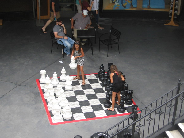 People congregate in a Horton Plaza nook where giant chess pieces beckon.