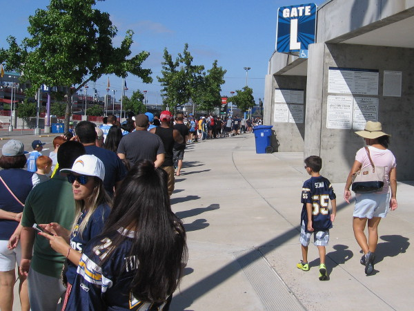 Thousands line up outside San Diego's Qualcomm Stadium to enjoy this year's Chargers FanFest. I saw many Seau jerseys being worn today.