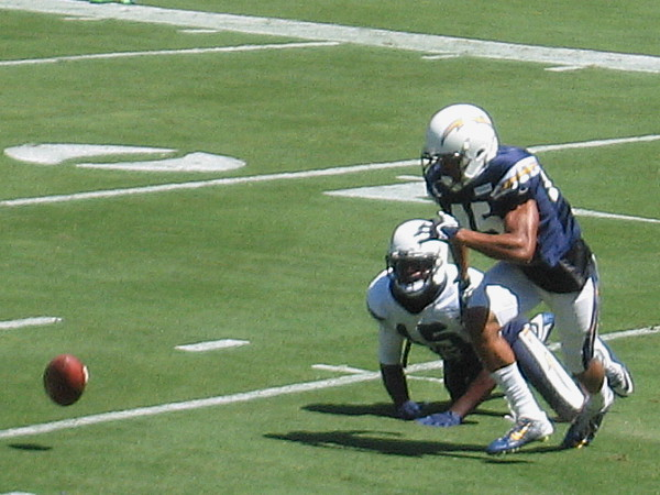 The pigskin bounces crazily on the grass as Chargers vie for possession.