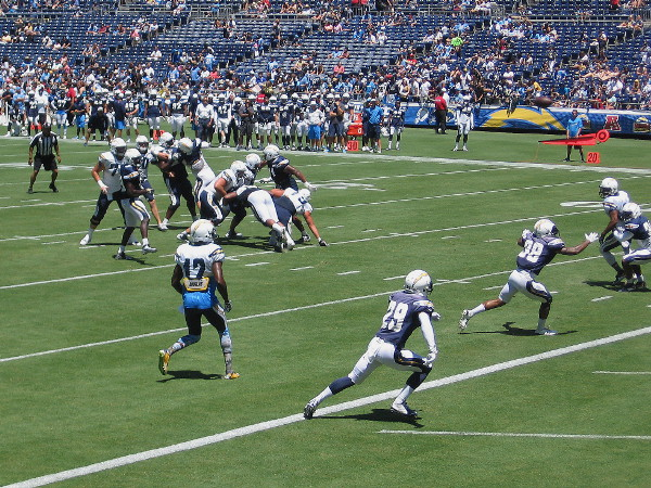 An exciting play near the end zone has players scrambling at full speed.