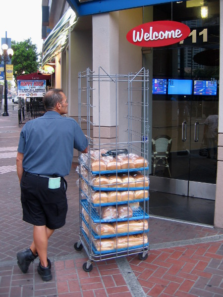 Delivery man with fresh bread awaits morning opening of restaurant in the Gaslamp Quarter.
