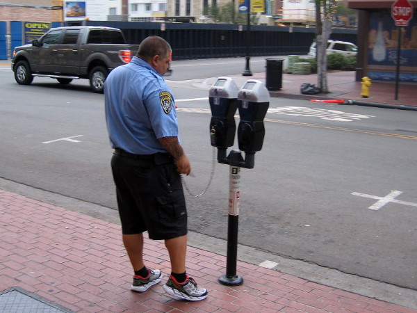 City employee checks parking meters before the streets become much busier.