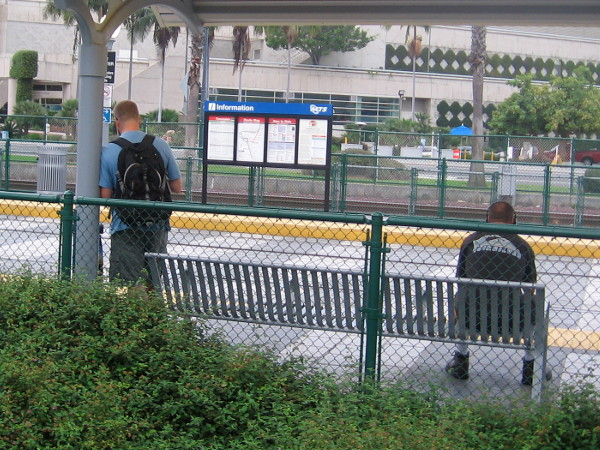 Early morning commuters await separately at the Convention Center trolley station.