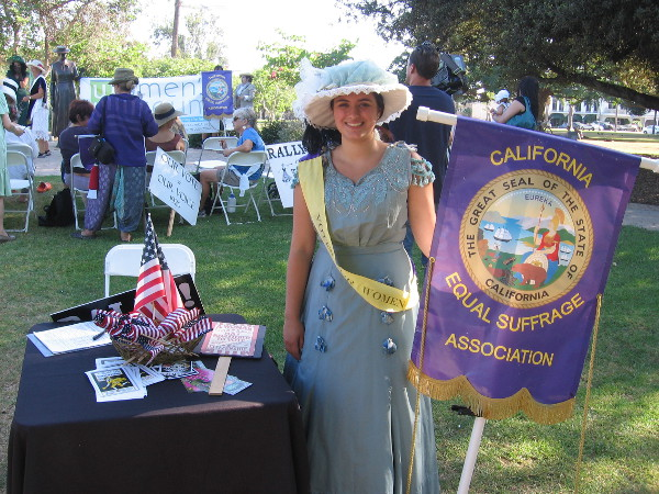 A smile, a Votes For Women sash, and a California Equal Suffrage Association banner.